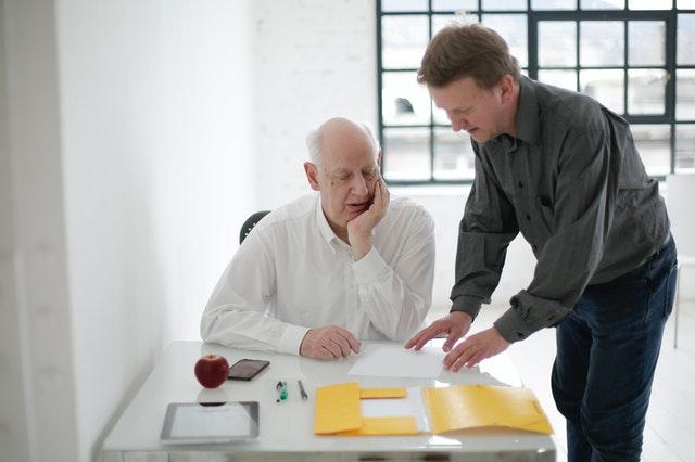 Senior a mladík nad dokumentem. Stáhněte si vzorový formulář pro výpověď nebo odstoupení od smlouvy.