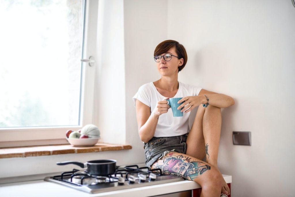 Dívka sedí a popíjí na plynovém sporáku