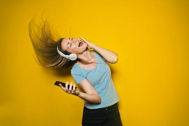 Žena poslouchá hudbu přes bezdrátová sluchátka, dodavatelé elektřiny 2021