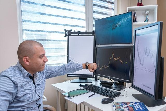 Investor sleduje burzu přes počítač